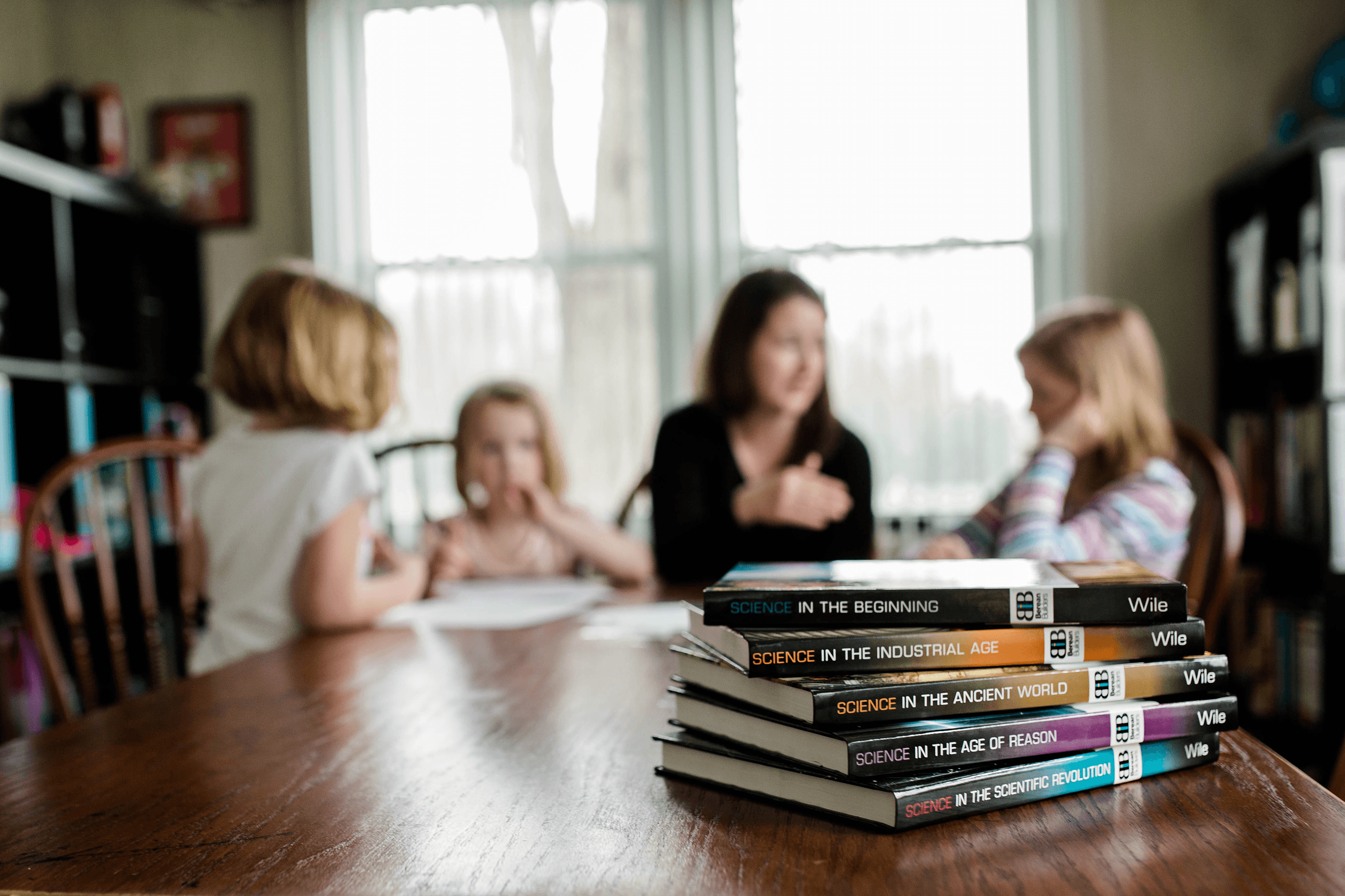 A stack of Berean Builders Elementary courses sits atop a dining table in the foreground while a mother speaks with her daughters around the table in the background