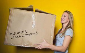 Uśmiechnięta kobieta przenosi karton ze spakowanymi rzeczami z kuchni
