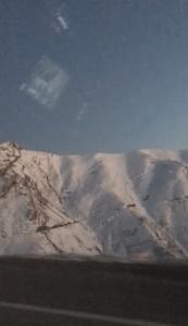 Bembeyaz, karla örtülü dağlar var yol kenarında.