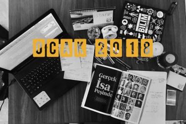 Bir çalışma masası üzerinde laptop, iki dergi, kitaplar defterler ve dağınık kalemler var. belli ki birileri çok çalışmış yine.
