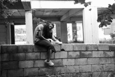Bir bahçe duvarı üzerinde oturmuş, bir ayağımı duvarın üzerine koymuş diğerini aşağı sarkıtmışım. altımda gri bir şalvar üzerimde kırmızı beyaz çizgili bir tişört var ama fotoğraf siyah beyaz. Bağımı, duvarın üzerine koyduğum bacağımın dizine yaslamışım. Saçlarım açık, kabarık.