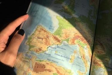Görselde elimde tuttuğum bir derginin açık bir sayfası var. sayfada ispanya haritası var ve Madrid, Barcelona büyük harflerle belirgin şekilde üstüne yazılmış. Derginin yarısına güneş ışığı vuruyor üst kısmı gölge.