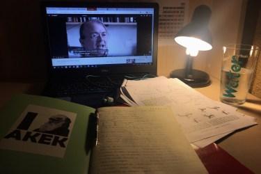 Görselde çalışma masam var. ışıkların kapalı olduğu karanlık bir odada sadece bilgisayar ışığı ve küçük masa lambası açık. masada bir defter ve birkaç kağıt var.