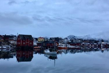 Norveç!te göl kenarındaki evler. Kırmızı ve beyaz küçük kulübe tipi evler var ve görüntüleri göle yansımış. göl ve gökyüzü aynı renk, neredeyse beyaz. evlerin aralarında beyaz küçük kayıklar var.