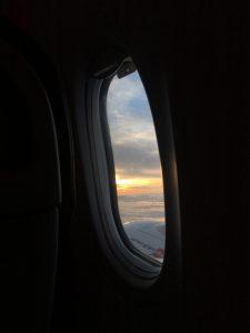 uçağın yuvarlak penceresinden bulutlar görünüyor ve bulutların arasından güneş ışığı sarı-turuncu olarak sızıyor.