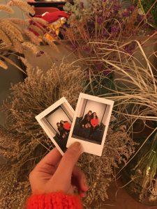 Görselde elimde tuttuğum iki tane küçük dikdörtgen şeklinde polaroid fotoğraf var. Arkada sarı renkli birkaç bitki görünüyor, kurumuş samana benziyorlar. Fotoğrafların ikisinde de ben ve arkadaşım bir basamağa oturmuşuz yan yana ve ben ona yaslanmışım, üzerime turuncu bir kazak ve siyah bir pantolon var. Clara da kot etekli ve uzun siyah bir palto giymiş. fotoğraflar çok küçük ve uzak olduğu için net görünmüyor fakat genel hatları ile bu şekilde görünüyor.
