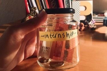 """görselde elimde tuttuğum cam bir kavanoz var. kavanozun içinde bozuk paralar ve 1 tane kağıt para var. kavanozun üstüne sarı bir post-it kağıt yapıştırılmış ve üzerinde siyah kalemle """"internship"""" yazılmış"""