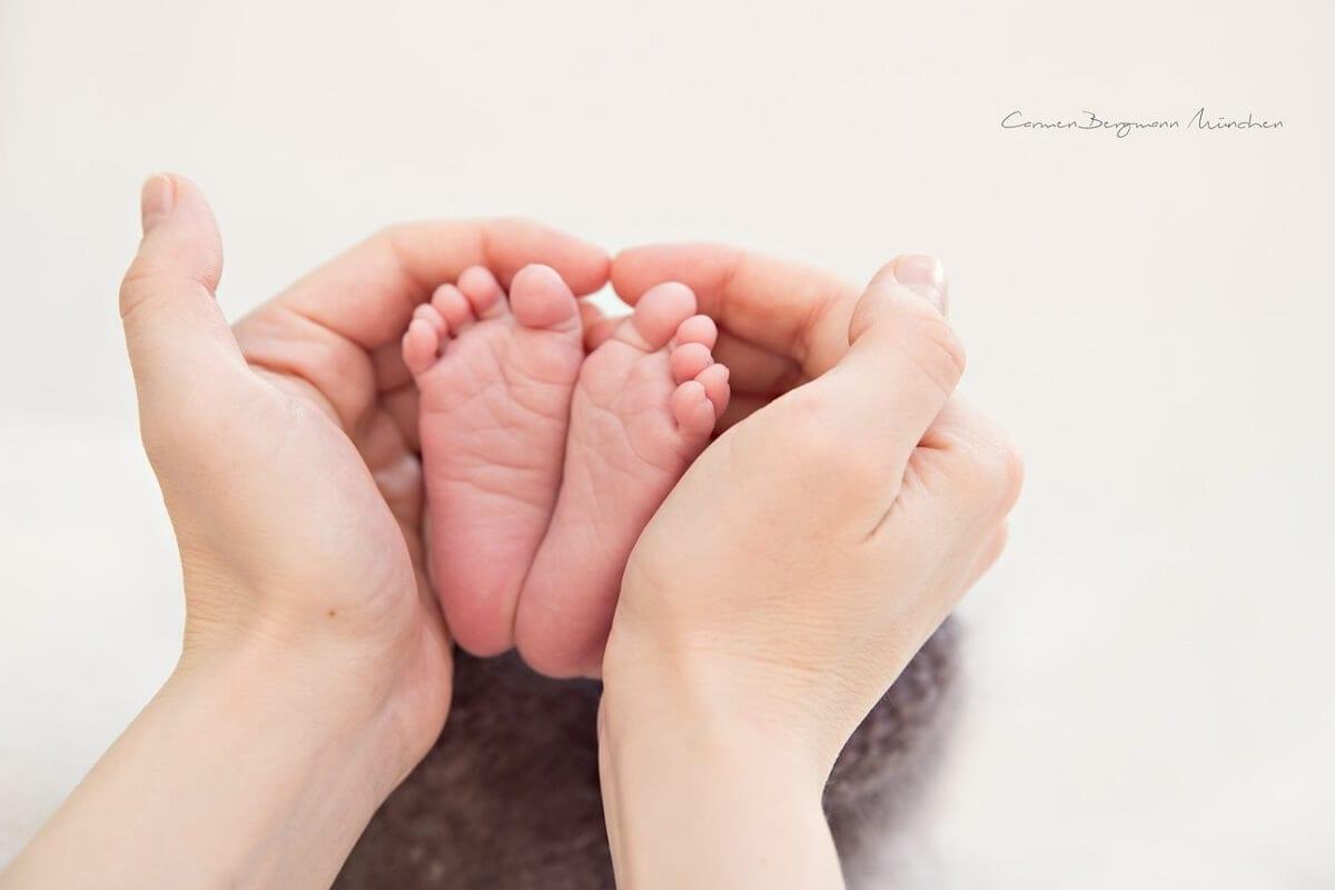 Kleine Fuesse von Neugeborenem Kind mit Haende der Mutter bei Fotoshooting in Fotostudio