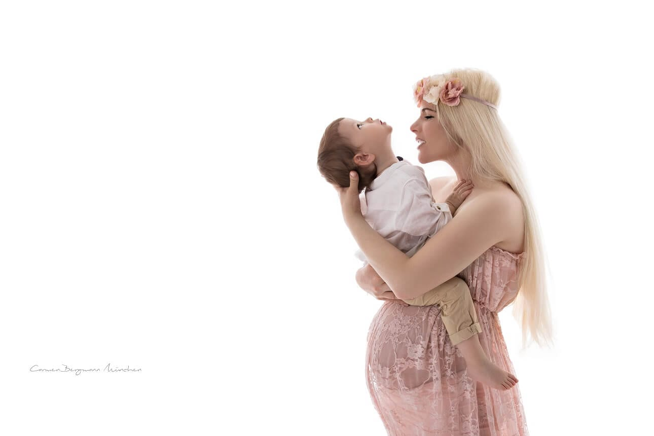 Schwangerschaftsfotografin in Muenchen Carmen Bergmann Kind und schwangere in rosa Kleid mit Partner