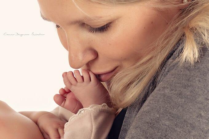 Neugeborenes wird von einer Mutter gekuesst, die ihn beim Fotoshooting in Carmen Bergmann in Haidhausen festhaelt