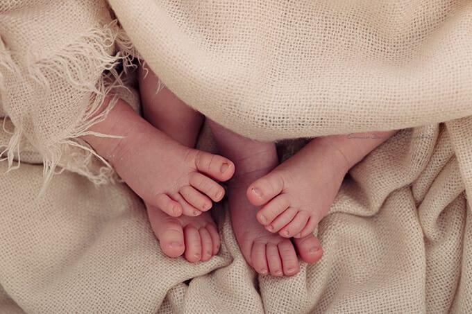 Zwilinge Fuesse Neugeboirenen Babies auf Decke im Fotostudio Muenchen Carmen Bergmann