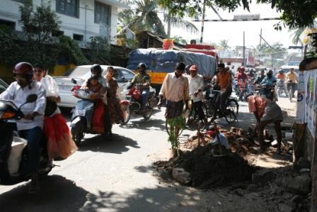 Soendagstrafik lige efter kirketid. Vejarbejderne er aabenbart hinduister.
