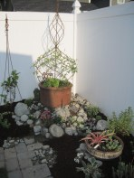 """Getting the """"bones"""" of a pocket garden right are the key to beautiful growth. Here, containers and supports are combined with a surrounding rock garden."""