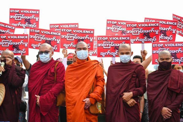Kelompok Biksu Buddha berdiri di depan pengunjuk rasa memegang tanda selama demonstrasi menentang kudeta militer di Yangon, pada 14 Maret 2021 FOTO: AFP
