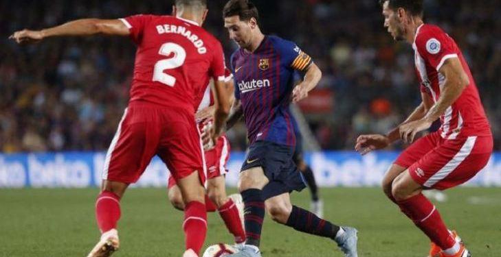 Lionel Messi mencoba melewati penjagaan dua pemain lawan saat Barcelona vs Girona dalam pertandingan lanjutan La Liga Spanyol di Camp Nou, 23 September 2018.