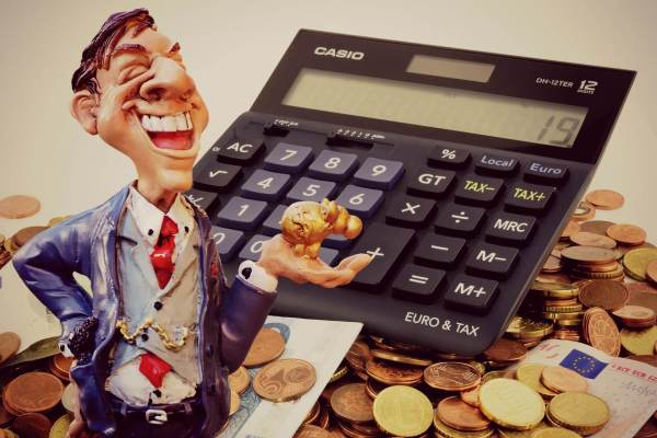 Businessman figurine in ftont of a pile of cash and a calculator