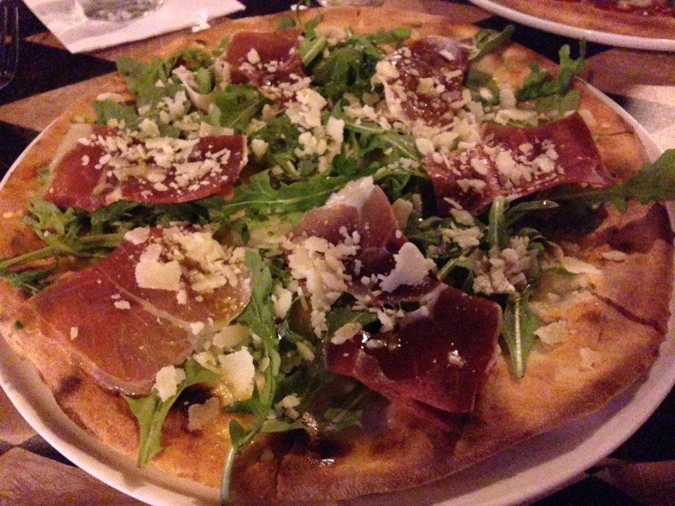 Photo of a pizza topped with cured ham, shaved cheese and arugula