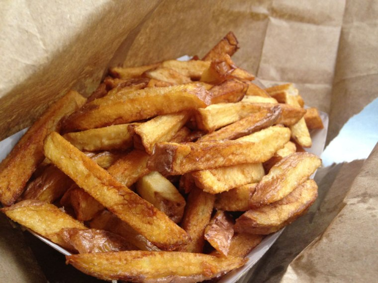 A close up photo of red-skin French fries in a paper cup