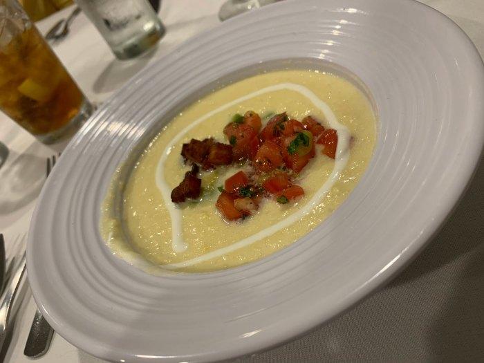 Corn soup topped with pico de gallo, pork belly and avocado crema