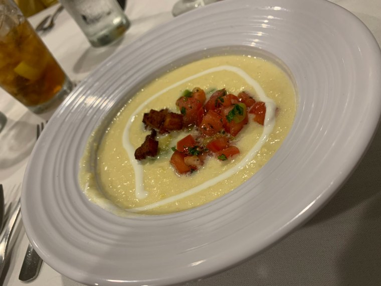 Corn soup topped with pico de gallo, pork belly and avocado crema