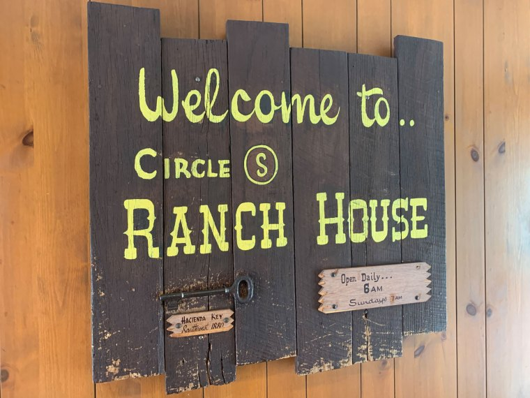 Inside, the decor is wood-on-wood, like this wooden Ranch House sign with wooden adornments mounted on a wood-paneled wall.
