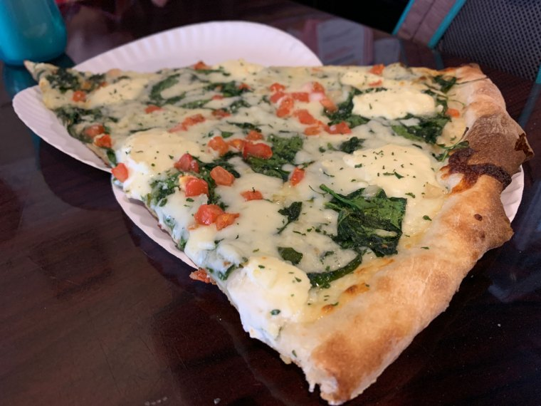 A slice of Frank white pizza, topped with ricotta, tomato and spinach
