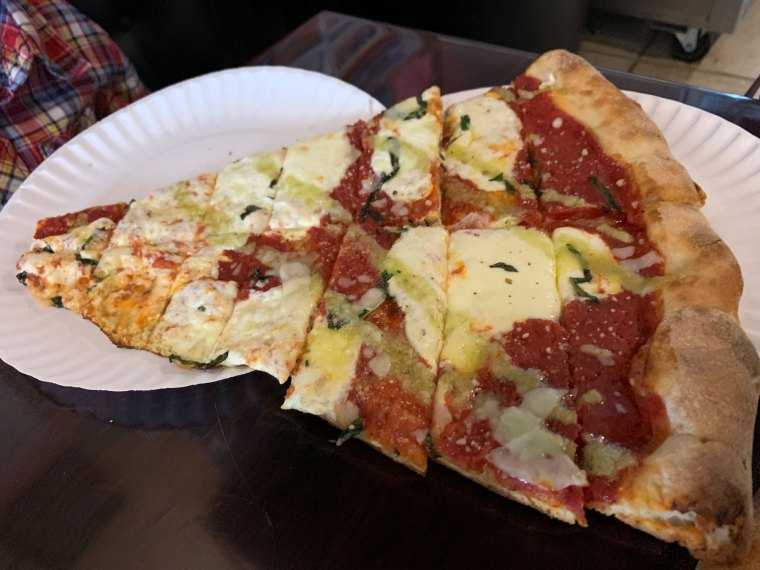 A slice of margherita pizza cut into smaller pieces