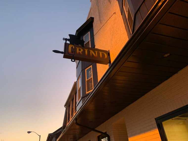 The exterior of Grind (Boyertown) in twilight, highlighted by their sign in the shape of a meat grinder.