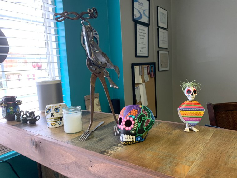 A skull and other sculptures sit on the counter at Comalli Taqueria