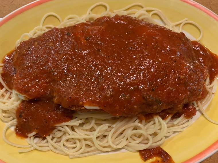 An order of chicken Paremsan, featuring an extra large chicken breast topped with red sauce on a bed of spaghetti, from Temple Family Restaurant.