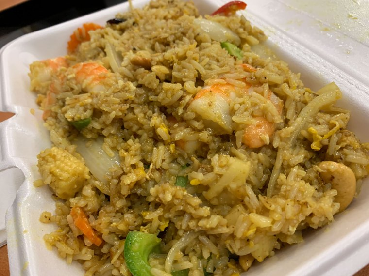 A styrofoam container of pineappel fried rice with shrimp and vegetables from Eve's Thai Kitchen.