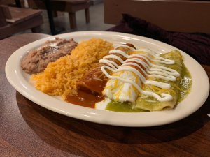 A plate with three enchiladas - one each with red, white and green sauce, with refried beans and rice from Norte Sur