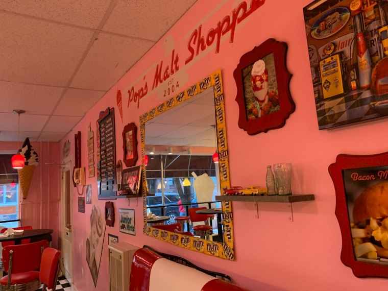 A close-up of the retro signs and a mirror on a pink wall in Pop's Malt Shoppe