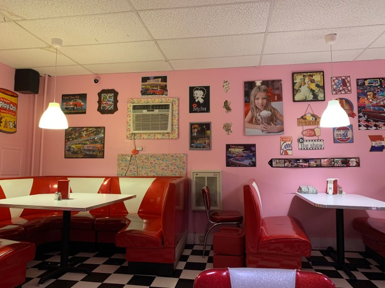 Red and white leather booths against a pink wall covered in retro signs in Pop's Malt Shoppe's dining room