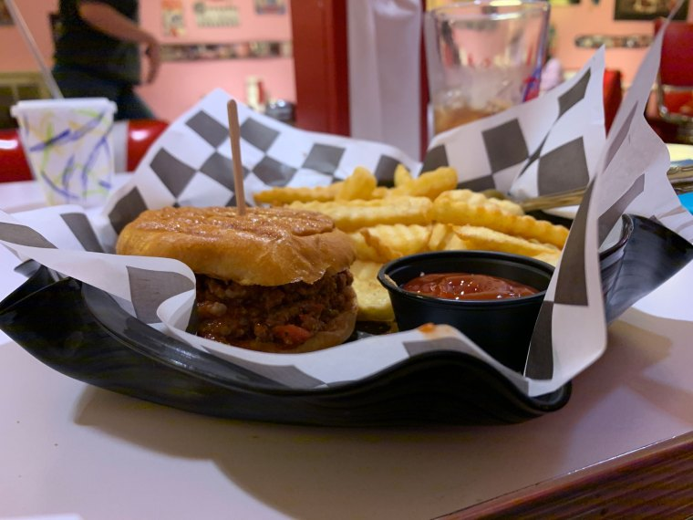 A sloppy Joe and fries with a cup of ketchup served on checkered paper atop a melted vinyl record plate