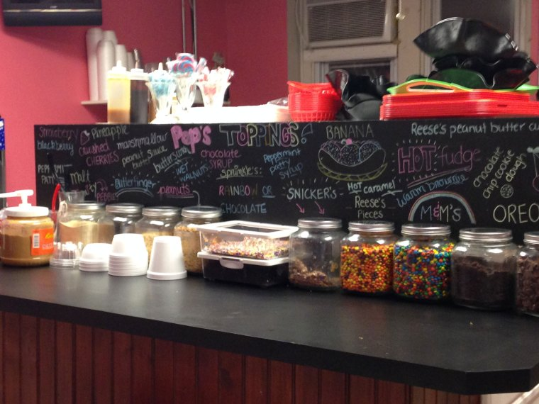 Jars of ice cream toppings in front of a chalkboard with toppings listed on it
