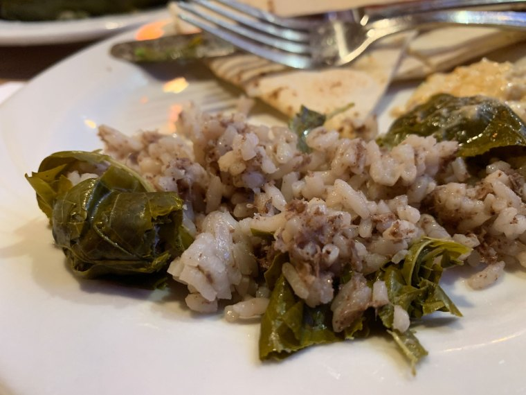 Stuffed grape leaves opened to show a mixture of seasoned rice and ground beef from Aladdin Mediterranean Restaurant