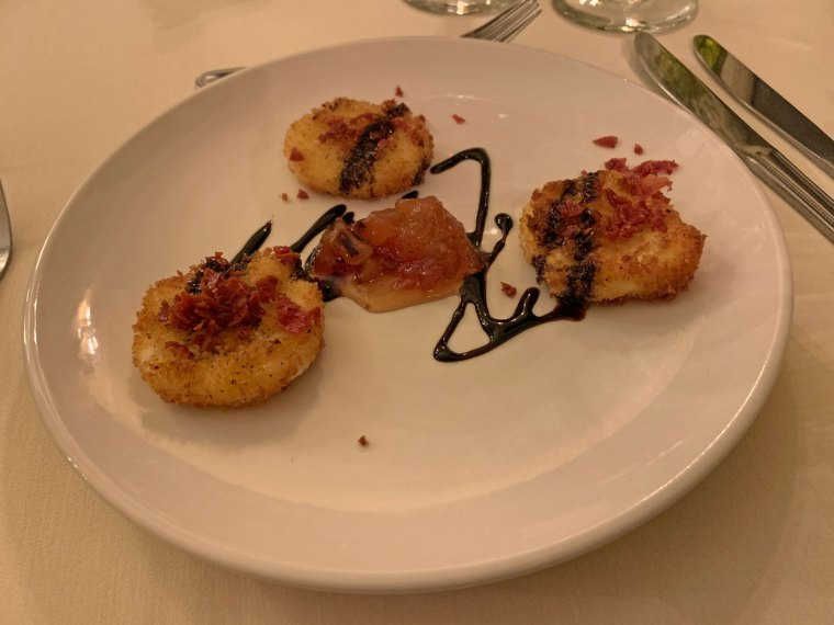A plate with three medallions of fried goat cheese with pear jam in the center and a balsamic drizzle from the Inn at Centre Park