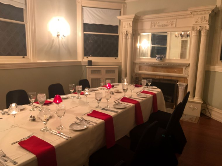 A private dining room with a table for 10 is set up in front of a fireplace at the Inn at Centre Park