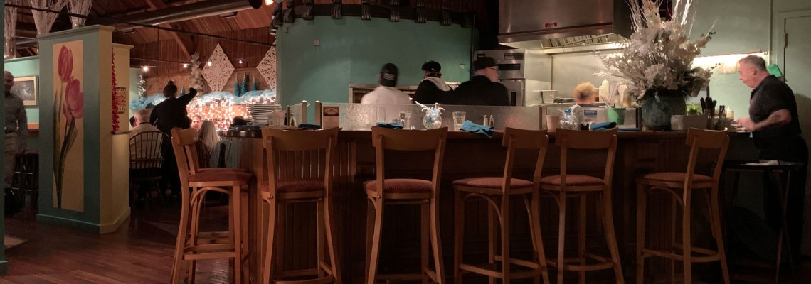 A view of the open kitchen, surrounded by a bar with stools at Judy's on Cherry