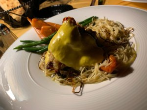Limoncello chicken - a plate of capellini pasta topped with a chicken breast covered in a yellow safron aioli from Judy's on Cherry