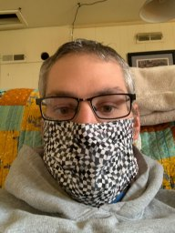 selfie of a man with glasses wearing a checkered flag mask