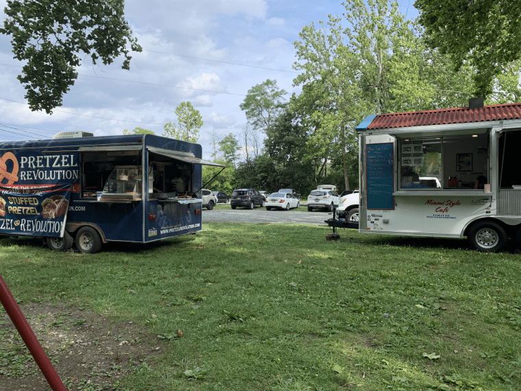Food trucks parked on a lawn with cars in the background