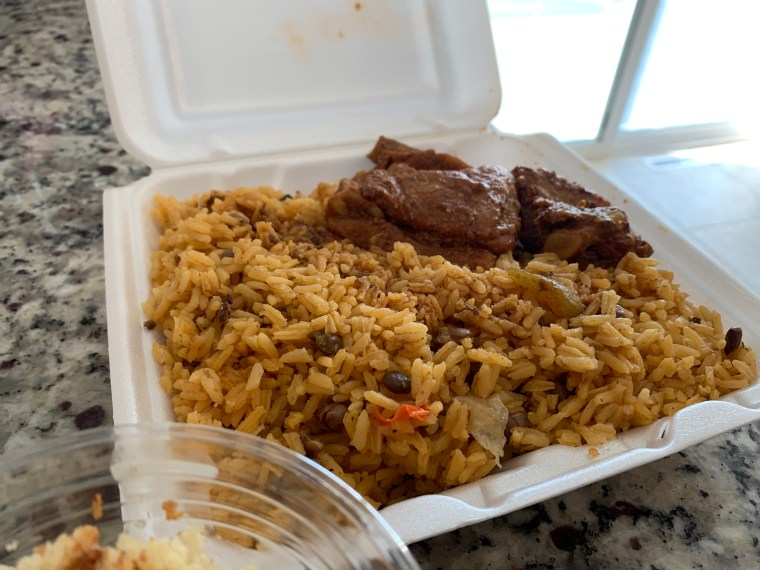 Photo of a takeout container filled with rice and beans and pork ribs