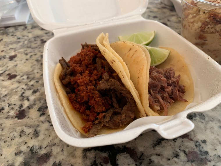 Photo of two tacos on corn tortillas. One is topped with beef and chorizo, the other is topped with shredded beef.