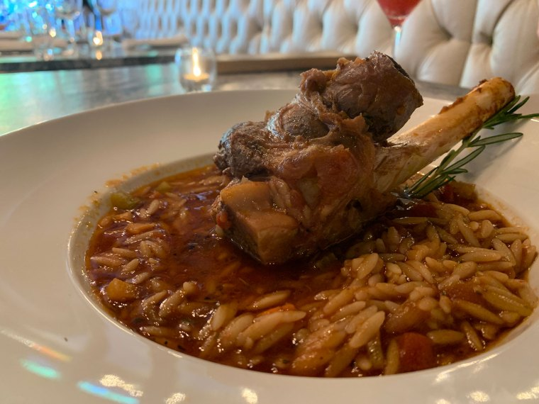 A white bowl filled with orzo in tomato sauce with a large bone-in lamb shank in the center.