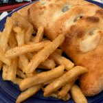 A photo of a calzone and French fries on a dark blue plate.