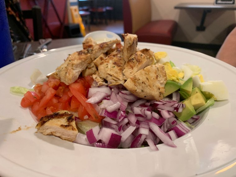 Photo of a Cobb salad topped with grilled chicken. Piles of red onions, diced tomatoes and avocado can be seen.