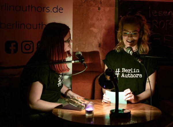 """Das Bild zeigt Katha, die Sophie bei einer Lesung interviewt. Die beiden sitzen an einem Tisch bei dämmriger Beleuchtung. Sie tragen schwarze T-Shirts, auf denen in weiß """"#BerlinAuthors"""" steht."""