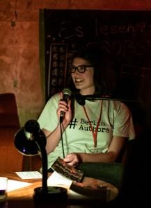 Teammitglied Liv: Braunhaarige Frau mit Brille, Anfang Zwanzig, sitzt an einem Tisch und spricht lächelnd in ein Mikrofon